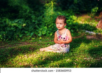 Little 3 years old short haired girl in gray dress sits on green grass in garden with small pink elephant toy. Sad child in summer time. Allergic. Sunset. Natural light.