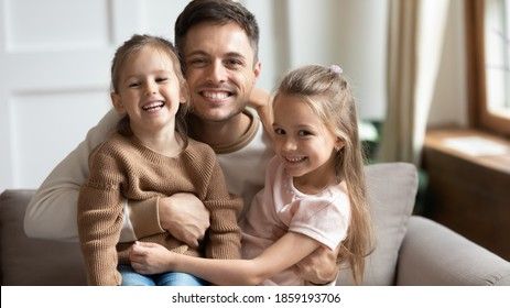 Little 6s 7s daughters sitting on daddy laps at home smile look at camera. Loving dad hugging pretty kids pose for picture, capture moment for family album. People celebrating Happy Father Day concept