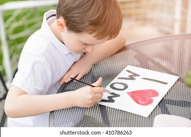 Little 7 year old boy paints greeting card for Mom on Mother's Day with the inscription