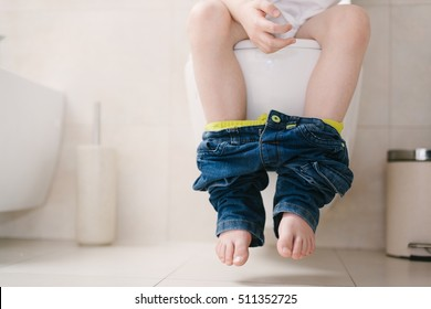 Little 7 years old boy on toilet. Low view on his legs