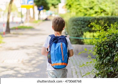 Little 7 years schoolboy going to school. Dressed in white t shirt and shorts. Blue backpack