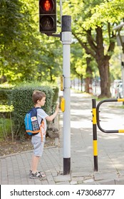 Little 7 years schoolboy pressing a button on traffic lights and waiting for green light. Dressed in white t shirt and shorts. Blue backpack with watercolors paints