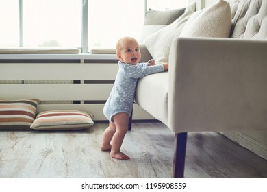 Little 8 months baby boy stands with support near sofa at home in white room