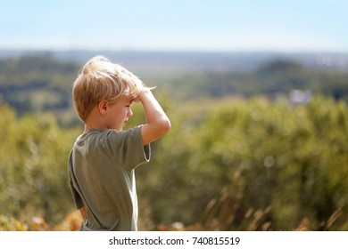 A little 8 year old boy out on a nature hike, is shielding his eyes from the sun as he looks out over the trees while high up on a bluff.