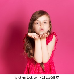 Little 8 years old girl make kissing gesture with her hands on a pink neutral background. She has long brunette hair and wear red summer dress. Funny expression on her face