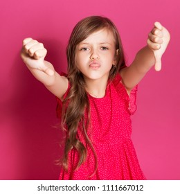 Little 8 years old girl make thumbs down gesture with her hands on a pink neutral background. She has long brunette hair and wear red summer dress. Funny expression on her face
