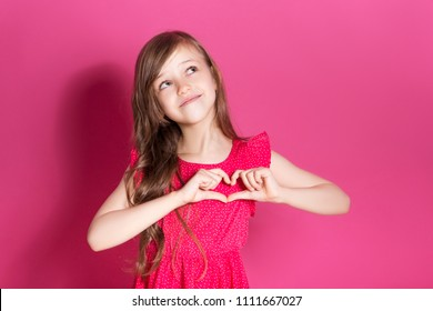 Little 8 years old girl make heart gesture with her hands on a pink neutral background. She has long brunette hair and wear red summer dress. Funny expression on her face