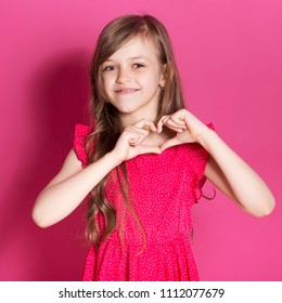 Little 8 years old girl make a heart gesture with her hands on a pink neutral background. She has long brunette hair and wear red summer dress. Funny expression on her face