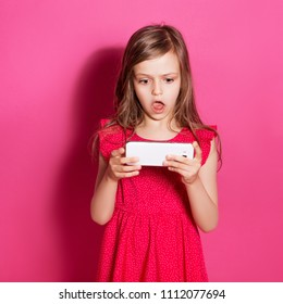 Little 8 years old girl make amazed gesture holding her phone on a pink neutral background. She has long brunette hair and wear red summer dress. Funny expression on her face