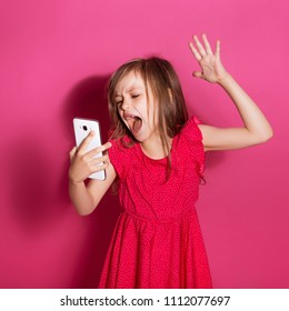 Little 8 years old girl make angry gesture holding her phone  on a pink neutral background. She has long brunette hair and wear red summer dress. Funny expression on her face