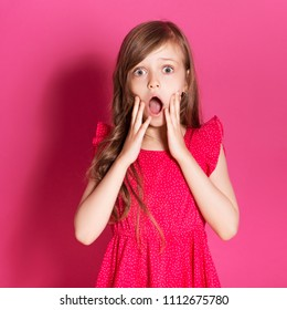 Little 8 years old girl make amazed or scared gesture with her hands on a pink neutral background. She has long brunette hair and wear red summer dress. Funny expression on her face