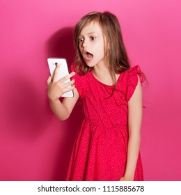 Little 8 years old girl make video chat on  her phone on a pink neutral background. She has long brunette hair and wear red summer dress. Funny expression on her face