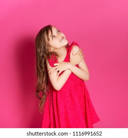 Little 8 years old girl make hug gesture with her hands on a pink neutral background. She has long brunette hair and wear red summer dress. Funny expression on her face