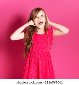 Little 8 years old girl make talking on a phone gesture with her hands on a pink neutral background. She has long brunette hair and wear red summer dress. Funny expression on her face