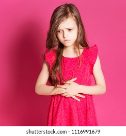 Little 8 years old girl make stomach pain gesture with her hands on a pink neutral background. She has long brunette hair and wear red summer dress. Funny expression on her face
