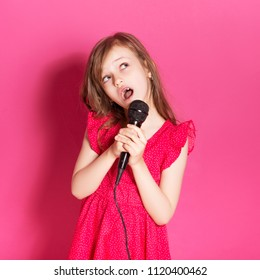 Little 8 years old girl singing in microphone on a pink neutral background. She has long brunette hair and wear red summer dress. Funny expression on her face