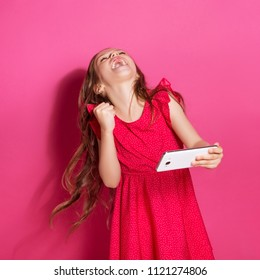 Little 8 years old girl make winning gesture holding her phone on a pink neutral background. She has long brunette hair and wear red summer dress. Funny expression on her face