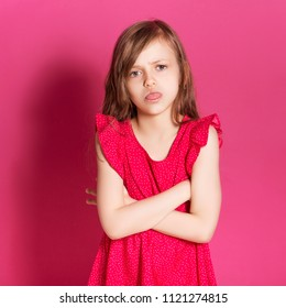 Little 8 years old girl make angry gesture with her hands on a pink neutral background. She has long brunette hair and wear red summer dress. Funny expression on her face