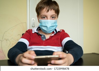 Little 9 year old boy in home isolation because of Covid 19 virus, wearing protective mask and playing video games on his cellphone.