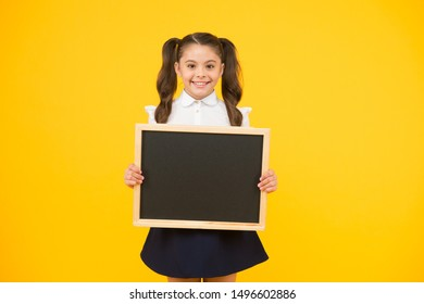 Little ad maker. Little schoolchild holding blackboard on yellow background. Little child with black-board for school advertisement. Little girl with empty chalkboard for your text, copy space.