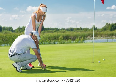 Little adjustments. Shot of a man placing a golf ball and tee in the ground in front of his woman