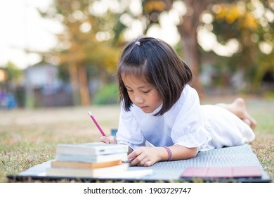 Little adorable Asian kid lying down on mat writing on notebook, Concept of outdoor education, A girl doing her homework, Kid like reading book