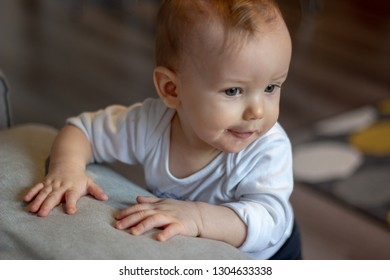 little adorable babyboy is standing holding the grey sofa and is thinking with furtive amused smile on his face