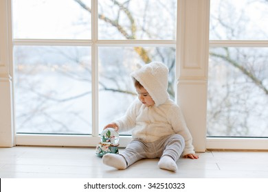Little adorable boy baby clothing white teddy bear sitting near the window, holding a ball in the interior of the house