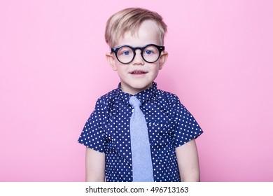 Little adorable boy in tie and glasses. School. Preschool. Fashion. Studio portrait over pink background