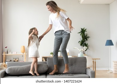 Little adorable daughter happy young mommy elder sister or babysitter hold hands jumping together on sofa in living room at home. Cheerful mom cute excited child spend free time on weekend having fun