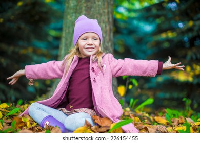 Little adorable girl in autumn park on sunny fall day