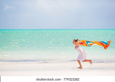 Little adorable girl with beach towel during tropical vacation