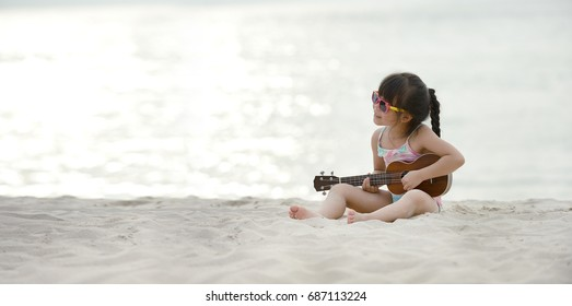 Little adorable girl play on Hawaiian Guitar or Ukulele. At white sand beach sea background. Space for text.