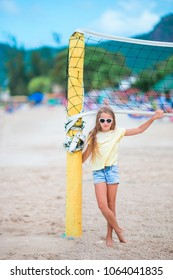 Little adorable girl playing voleyball on beach with ball.