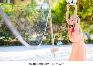 Little adorable girl playing voleyball on beach with ball. Sporty family enjoy beach game outdoors