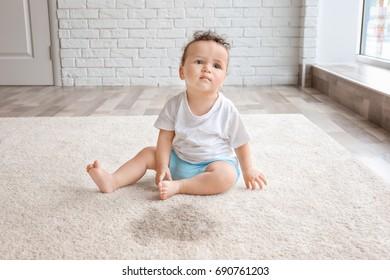 Little adorable girl sitting on carpet near wet spot