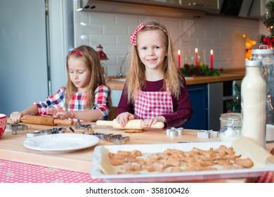 Little adorable girls baking gingerbread house on Christmas eve