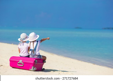 Little adorable girls with big suitcase on tropical white beach during summer vacation