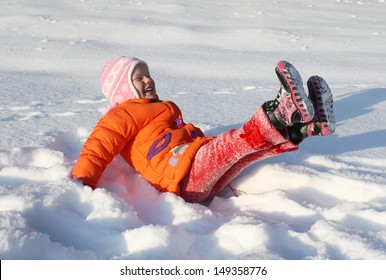 Little adorable happy girl falling into fresh clean snow. Child in an orange coat and cap playing outdoors in winter park. Sunny weather.