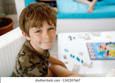 Little adorable school kid boy playing board game with family. Schoolkid and child having fun with active game.