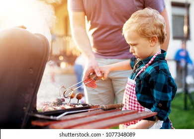 Little adorable toddler boy is being guided by his father how to use cooking clip and grill.