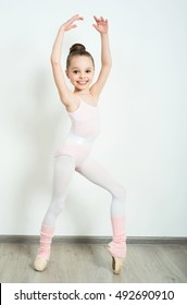 A little adorable young ballerina does ballet poses and stretching exercises on the floor at home