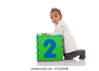 Little African American baby girl playing with construction games isolated on white background