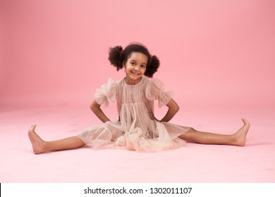 Little African American ballerina on pink background