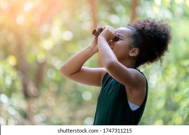 Little African American Girl with Binoculars during Hiking in Forest. Happy Kid playing Outdoors in Summer day. Girl Using binoculars in the Jungle.
