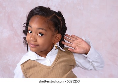 A little African American girl cupping her hand to her ear listening