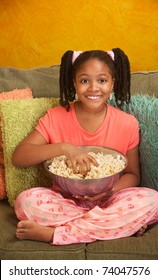 Little African American girl eats from a bowl of popcorn