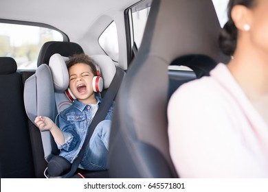 little african american girl listening music with mother sitting in car