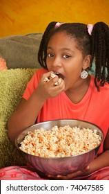 Little African American girl in pajamas eats popcorn