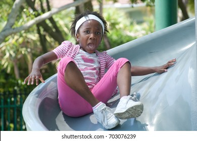 Little African American girl scared going down a slide